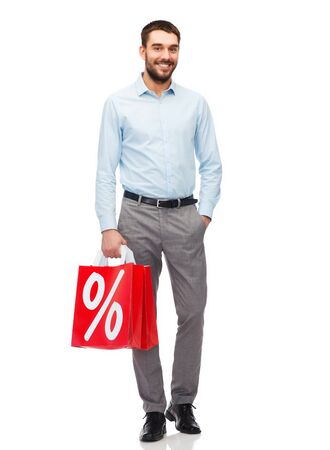 percentage sign: people, sale, discount and holidays concept - smiling man holding red shopping bags with percentage sign