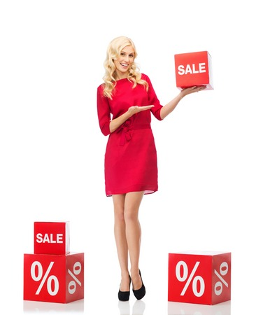 percentage sign: people, shopping, discount and holidays concept - smiling woman in red dress holding cardboard box with sale and percentage sign