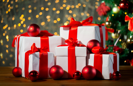 under tree: christmas, holidays, presents, new year and celebration concept - group of gift boxes and red balls under x-mas tree on wooden floor Stock Photo