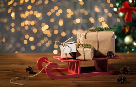 christmas tree presents: holidays, presents, new year and celebration concept - close up of gift boxes with blank note on red wooden sleigh over christmas tree and lights background