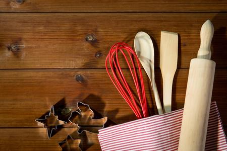 trompo de madera: hornear, cocinar, la Navidad y el concepto de cocina de la casa - cerca de conjunto de cocina para la cocción de pan de jengibre sobre tabla de madera de arriba