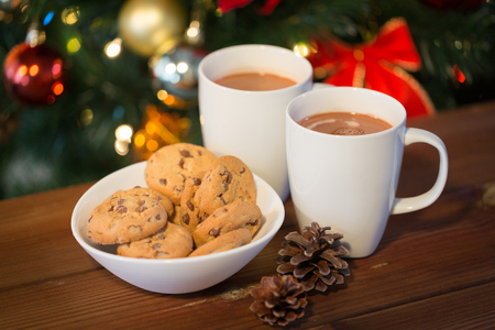 holiday cookies: holidays, winter, food and drinks concept - close up of oatmeal cookies, cups with hot chocolate or cocoa drink and pinecones on wooden table over christmas tree background