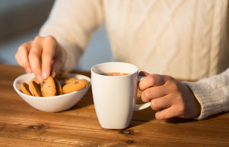 dessert: winter, food and drink concept - close up of woman with oat cookies and hot chocolate cup sitting at wooden table at home