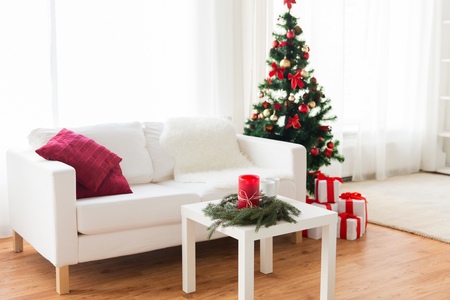 christmas candles: holidays, celebration, decoration and interior concept - sofa, table and christmas tree with gifts at home