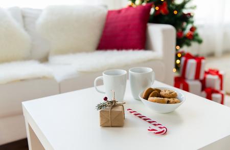 taza: navidad, d�as de fiesta y el concepto de invierno - cerca de regalo, galletas de avena, az�car bast�n de caramelo y tazas en la mesa en casa