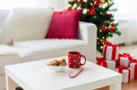 christmas, holidays, winter and celebration concept - close up of oat cookies, sugar cane candy and red cup on table at home Stock Photo