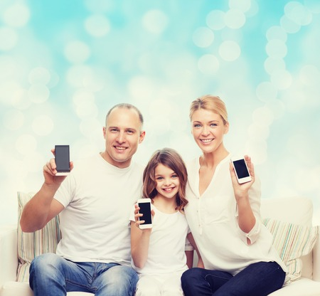 beautiful preteen girl: holidays, technology, advertisement and people concept - smiling family with smartphones over blue lights background Stock Photo