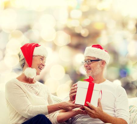 abuelos: familia, días de fiesta, navidad, la edad y el concepto de la gente - la feliz pareja senior con caja de regalo sobre fondo de las luces Foto de archivo