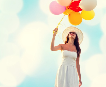 summer fun: happiness, summer, holidays and people concept - smiling young woman wearing sunglasses with balloons over blue lights background