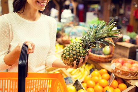 canastas de frutas: venta, compras, consumismo y el concepto de la gente - cerca de la mujer joven con canasta de alimentos y piña en el mercado de comestibles