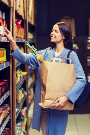 happy shopping: sale, shopping, consumerism and people concept - happy young woman with paper bag choosing and buying food in market Stock Photo