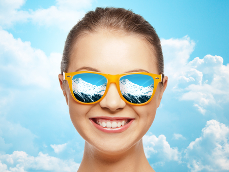 travel, tourism, winter resort and people concept - happy face of teenage girl in sunglasses with mountains reflection over blue sky and clouds background