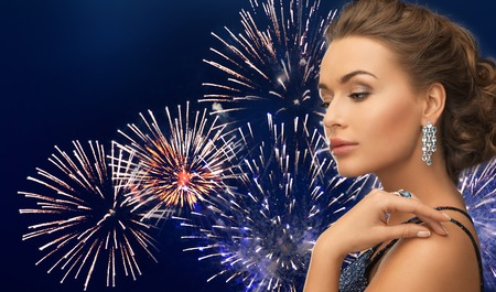 hollywood christmas: people, holidays and glamour concept - beautiful woman with diamond earring over firework on dark blue background