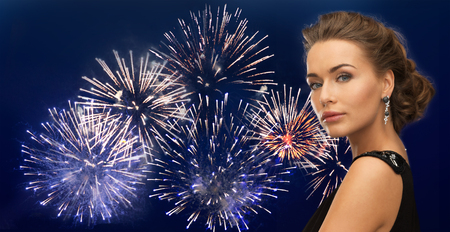 hollywood christmas: people, holidays and glamour concept - beautiful woman wearing earrings over firework on dark blue background