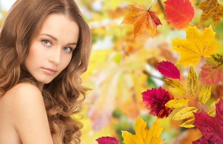 beauty and health: beauty, people, season and health concept - beautiful young woman face with long curly hair over autumn leaves background Stock Photo