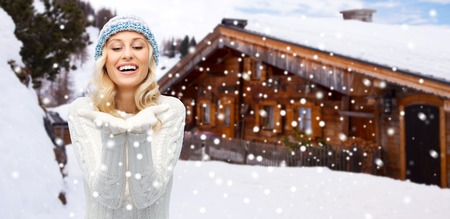 empty of people: winter, advertisement, vacation, christmas and people concept - smiling young woman in hat and sweater holding something on her empty palms over wooden country house and snowflakes background