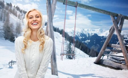 earmuffs: winter, vacation, christmas and people concept - smiling young woman in earmuffs and sweater over snowy mountains and wooden swing background