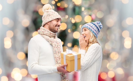winter, holidays, couple, christmas and people concept - smiling man and woman in hats and scarf with gift box over lights background Stock Photo - 49524959