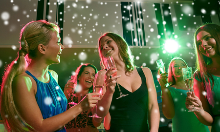 nonalcoholic: new year party, holidays, celebration, nightlife and people concept - happy young women with glasses of non-alcoholic champagne dancing in club and snow effect Stock Photo