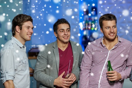 snow man party: nightlife, party, friendship, leisure and people concept - group of smiling male friends with beer bottles drinking in nightclub and snow effect Stock Photo