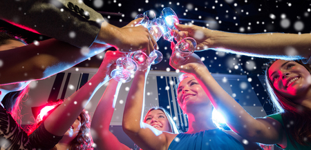 night out: new year party, holidays, celebration, nightlife and people concept - smiling friends with glasses of non-alcoholic champagne in club and snow effect Stock Photo