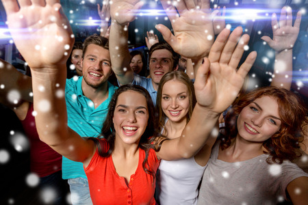 crowd people: party, holidays, celebration, friends and people concept - smiling friends dancing and waving hands in club and snow effect