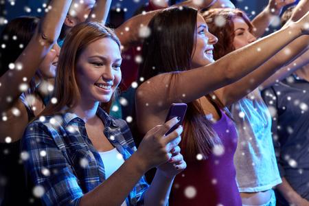 party, feiertage, feier, Nachtleben und Personen-Konzept - lächelnde junge Frau mit Smartphone SMS Nachricht am Konzert in Club und Schnee-Effekt