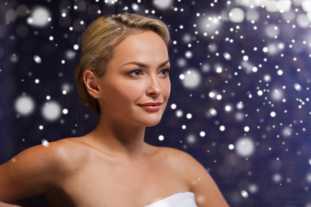 turkish woman: people, beauty, spa, healthy lifestyle and relaxation concept - beautiful young woman sitting in bath towel at sauna with snow effect