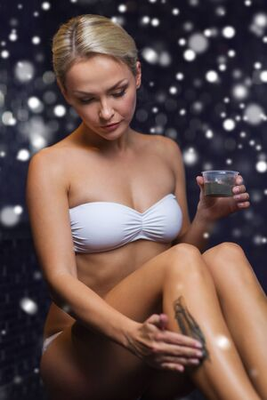 mud snow: people, beauty, spa, healthy lifestyle and relaxation concept - beautiful young woman in swimsuit applying therapeutic mud in bath or sauna with snow effect Stock Photo