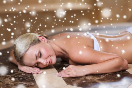 turkish bath: people, beauty, spa, healthy lifestyle and relaxation concept - beautiful young woman lying on hammam table in turkish bath with snow effect