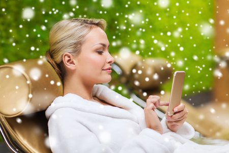 bath robe: people, beauty, lifestyle, technology and relaxation concept - beautiful young woman in white bath robe with smartphone social networking at spa with snow effect