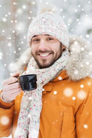 forest tea: season, christmas, drinks and people concept - happy smiling young man with cup drinking hot tea in winter forest Stock Photo