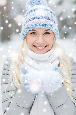 season, christmas and people concept - happy smiling young woman holding snow on palms in winter forest