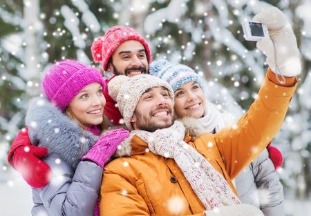 Tecnologia, la stagione, l'amicizia e la gente concetto - gruppo di sorridere uomini e donne che assumono Selfie con fotocamera digitale in inverno foresta Archivio Fotografico - 49526673
