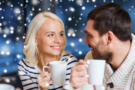 people, leisure, communication and season concept - happy couple meeting and drinking tea or coffee at winter cafe Stock Photo