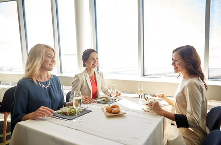 dinner party: people, holidays, celebration and lifestyle concept - happy women eating and drinking champagne at restaurant Stock Photo