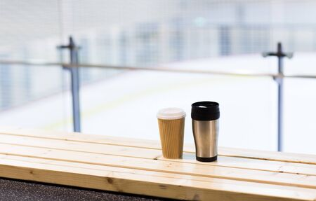 thermos: hot drink, winter and leisure concept - close up of coffee cup and thermos on wooden bench at skating rink arena