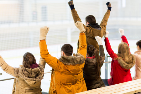leisure games: people, friendship, sport and leisure concept - happy friends watching hockey game or figure skating performance on ice rink arena Stock Photo