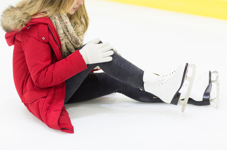 hurt: people, sport, trauma, pain and leisure concept - close up of young woman fell down on skating rink with knee injury holding to her leg