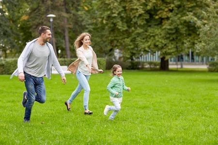 家族、親子関係、レジャーと人コンセプト - 幸せな母、父と少女を実行して、再生をキャッチ ゲーム夏の公園で 写真素材