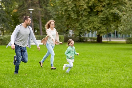 leisure games: family, parenthood, leisure and people concept - happy mother, father and little girl running and playing catch game in summer park Stock Photo