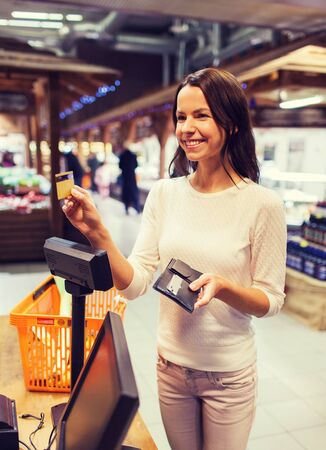 paying: sale, shopping, consumerism and people concept - happy young woman with credit card and wallet buying food at checkout in market
