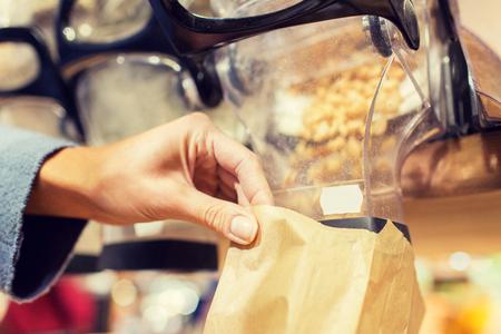 abarrotes: concepto de venta, compras y comida ecol�gica - cerca de la mano femenina vertiendo las tuercas a la bolsa de papel en la tienda de comestibles