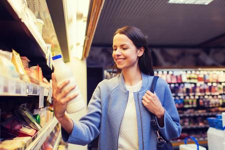 tomando leche: venta, compras, consumismo y las personas concepto - mujer joven feliz celebración de la botella de leche en el mercado
