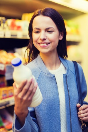 consumerism: sale, shopping, consumerism and people concept - happy young woman holding milk bottle in market