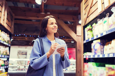 consumerism: sale, shopping, consumerism and people concept - happy young woman taking notes to notebook in market Stock Photo