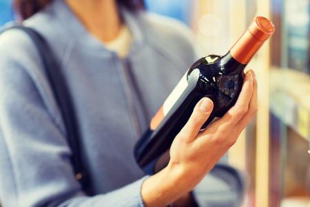Verkauf, Einkaufen, Konsum und Menschen Konzept - glückliche junge Frau, die Auswahl und Wein in Markt oder Spirituosengeschäft kaufen Standard-Bild - 49490126