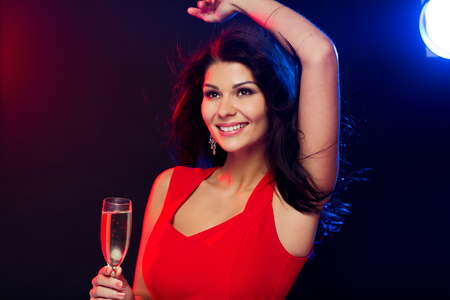 sexy dress: people, holidays, party,  night lifestyle and leisure concept - beautiful sexy woman in red dress with champagne glass dancing at nightclub