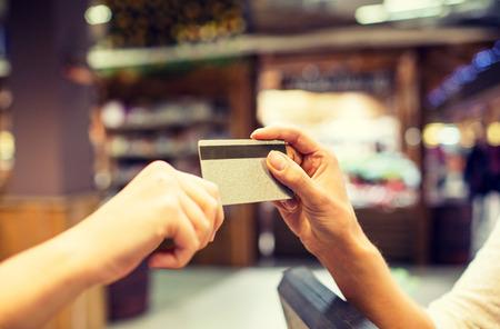 Verkauf, Einkaufen, Zahlung, Konsumdenken und Menschen Konzept - Nahaufnahme von H�nden Kreditkarte an der Kasse in Markt oder Mall geben