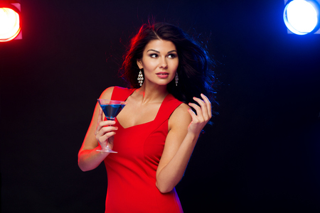 liquor girl: people, holidays, party, alcohol and leisure concept - beautiful sexy woman in red dress with cocktail glass dancing at night club